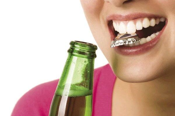 không cắn mở lắp chai để hạn chế biến chứng khi bọc răng sứ
